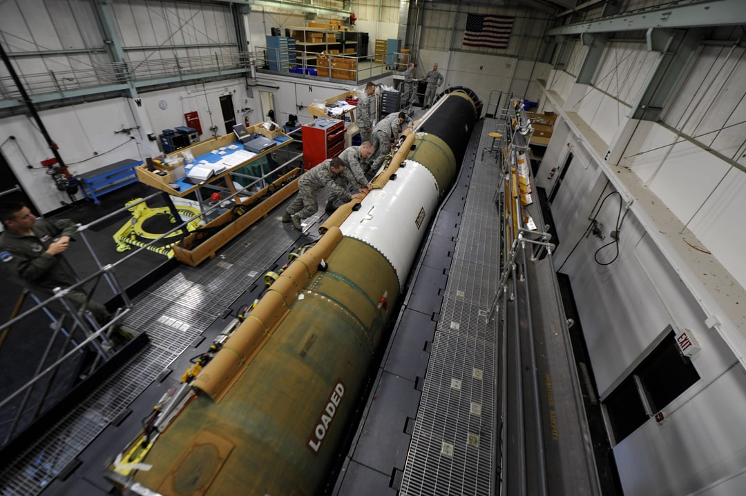 A LGM-30G Minuteman III being worked on by a crew of technicians.
