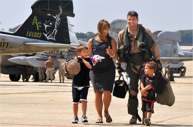 A man in uniform, a civilian woman and two children walk together on a flightline.
